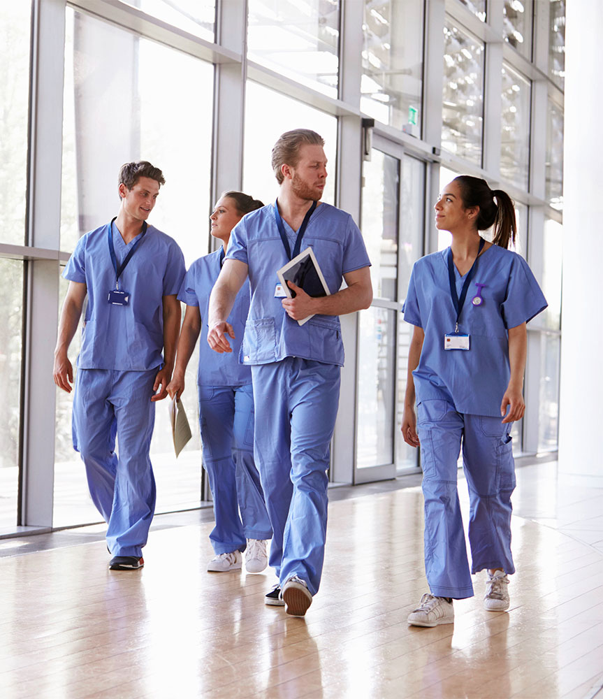 Group of nursing students walking down brightly lit hallway